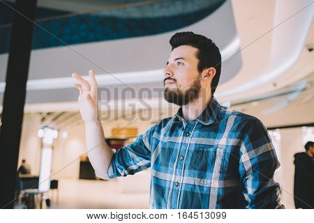 Young man in the shopping mall. Handsome guy is standing near sensor signboard and trying to choose some interesting shop proposition. Place for your advertisement