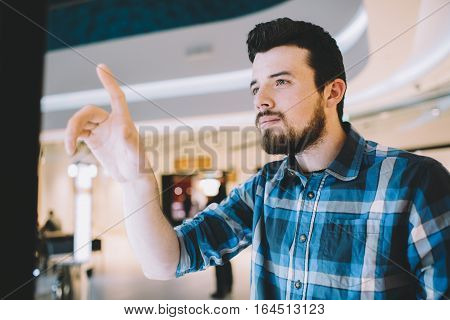 Young man in the shopping mall. He is trying to touch to screen and to choose the best proposition for him. Place for your advertisement. Close up