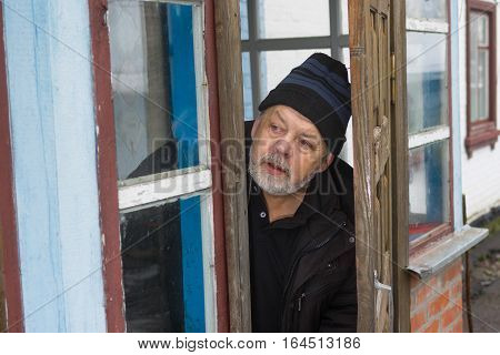 Ukrainian senior peasant peeping out from old house