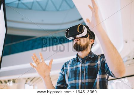 Young man trying vr goggles. Handsome guy watching some interesting virtual video or gaming and doing different gestures