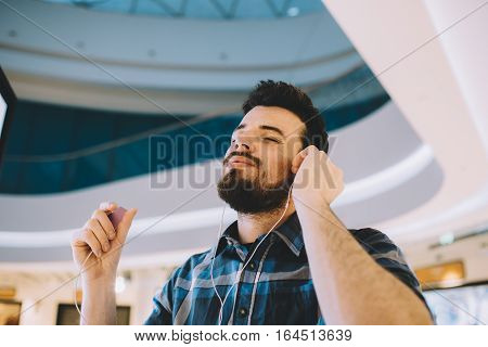 Portrait of a young handsome man with Mp3 and headphones in urban background. Attractive guy with beard is blissing out because he is listening only to his music. He is happy.