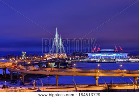 Saint-Petersburg Russia - December 28 2016: Cable-stayed bridge across the Petrovsky fairway at the mouth of the Little Neva and football stadium Zenit Arena with night illumination.