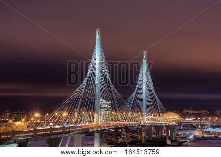 Saint-Petersburg Russia - December 28 2016: Pylons highway suspension bridge illuminated at night Cable-Stayed Bridge over Petrovsky Fairway St. Petersburg Russia.