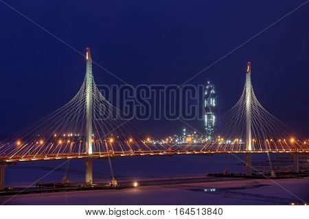 Saint-Petersburg Russia - January 2 2017: Night view of the Gazprom skyscraper tower under construction through the pylons of the cable-stayed bridge in the winter.