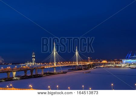Saint-Petersburg Russia - January 3 2017: A highway crosses the frozen river on a cable-stayed bridge night view with the tower skyscraper under construction.