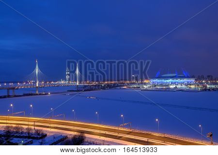 St. Petersburg Russia - January 2 2017: Night city in the winter the car cable-stayed bridge the football stadium skyscraper under construction and freeway.