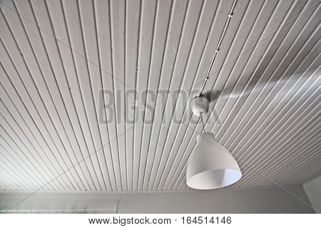 Abstract white interior with a lamp and a wood ceiling