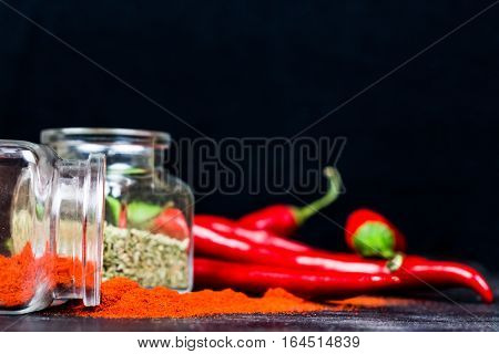 Chili powder, dry basil and chili peppers on black table. Paprika, oregano and red chili peppers in glass jars on dark wood background