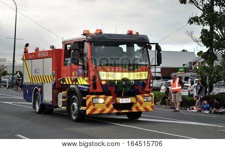 Fire truck driving slowly through the street in kumeu new zealand during a christmas street parade