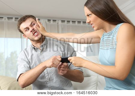Couple or friends fighting for a mobile phone sitting on a couch at home