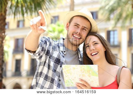 Couple of tourists consulting a guide map in the street of a touristic place during vacations with buildings and palm trees in the background