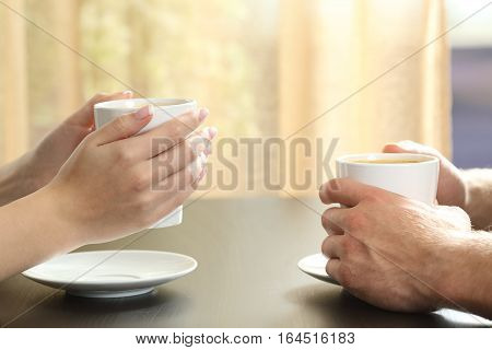 Close up of side view of a couple or friends talking with hands holding coffee cups on a table with a window and curtain in the background