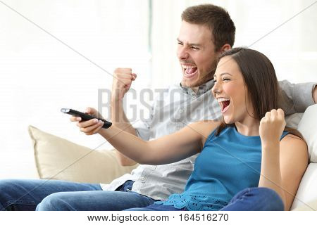 Excited couple watching tv together sitting on a sofa in the living room at home