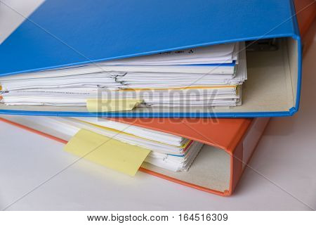 A orange and a blue binder isolated with documents.