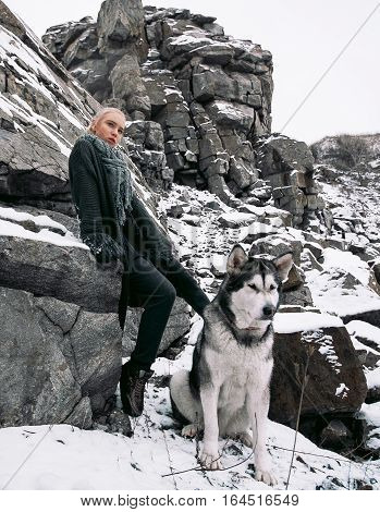 Girl with dog Malamute among rocks in winter. They sit on rocks among scattering of stones and snow.