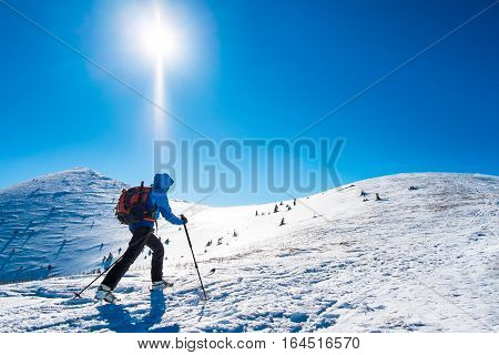 Tourist on trip in snowy mountains, background winter sport, winter sport for one, hiker sporting in winter