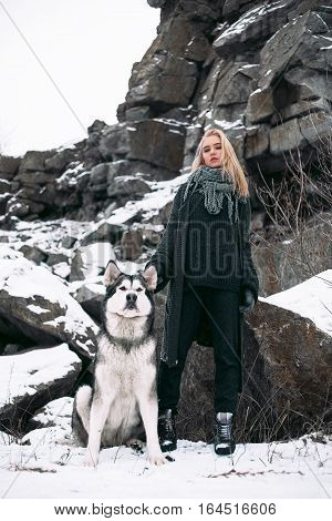 Girl with dog Malamute among rocks in winter. She is standing among rocks and snow. Dog sits next to her.