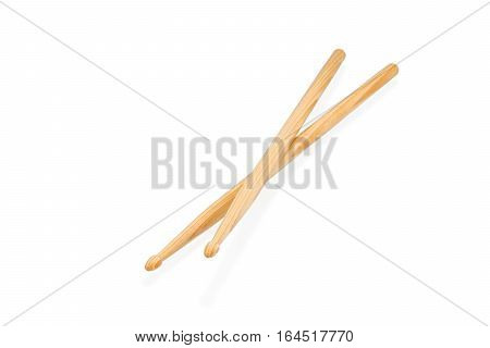 Two wooden drum sticks lying on each other isolated on white background