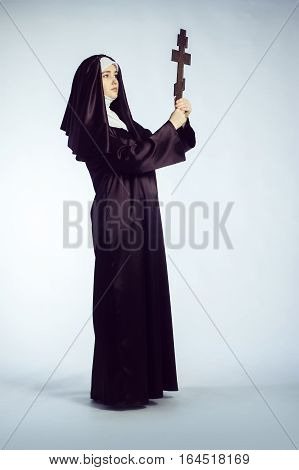 Full growth photo of young catholic nun with orthodox cross.