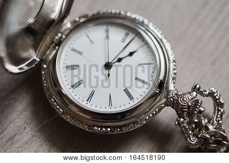 open pocket watch and chain lie on a light wooden table background