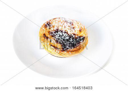 Egg tart or portuguese egg tart on white plate isolated on white background close up