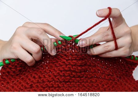 Girl's hands are knitting a red muffler out of wool with green knitting needles.