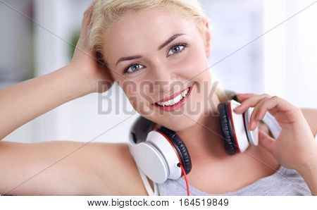 Portrait of young beautiful woman at home sitting on sofa and listening music
