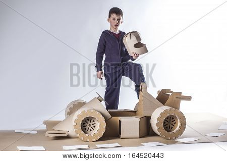photo of young racer on a cardboard racing car