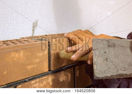 Bricklayer lays brick gently tapping with a trowel. construction work