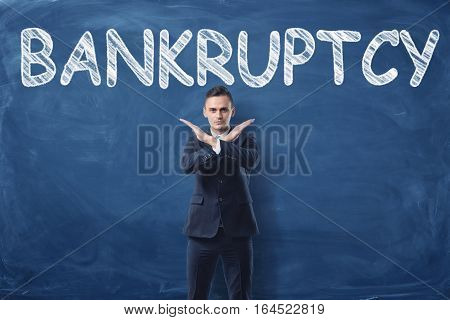 Businessman standing with his hands like a cross sign and a word Bankruptcy written on a blackboard behind him. Getting through the crisis. Business decisions. Confident behaviour.