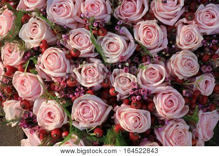 Pink roses and berries in a wedding arrangement