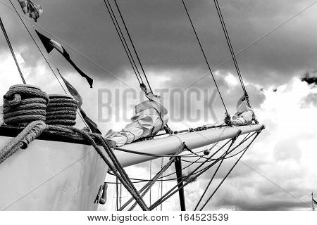 Details of Bowsprit and rope coiled up of the tall ship on the cloudy sky background. Concepts: prosperity, optimism, positive, future