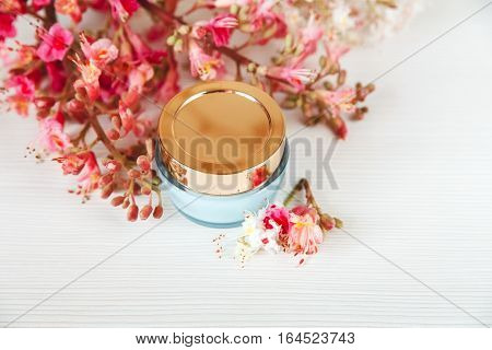 White and Pink Branches of Chestnut Tree with Blue and Golden Jar of Cream are on White Table.Top View