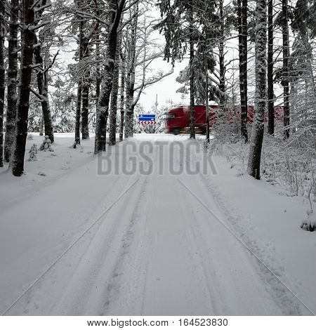 Car Tire Tracks On Winter Road With Road Signs