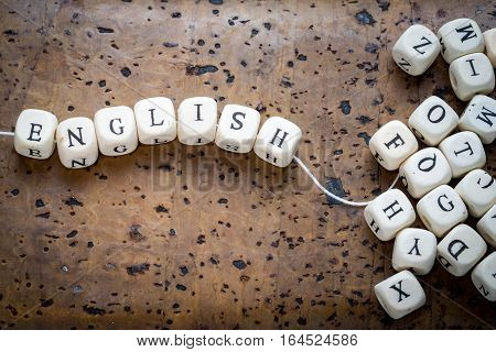 english word on a wooden cubes strung on a thread on a brown cork background stack of alphabet cubes copy space