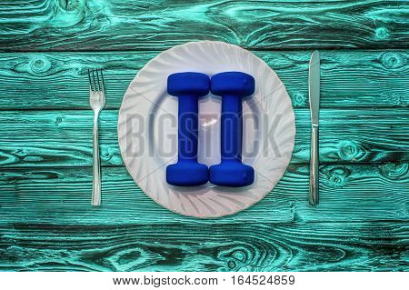 Dumbbells on a plate as a breakfast, concept of healthy lifestyle, on a wooden table