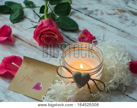 Burning candle and rose petals on vintage wooden table. Valentine's Day and Mother's Day background.