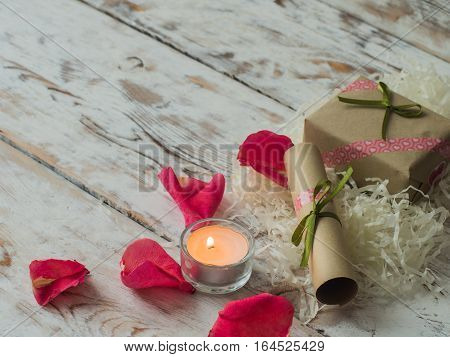 Valentine day. Candle and rose petals on a background of wood. Valentine's Day Gift. Space for text. Eighth of March. International Women's Day.