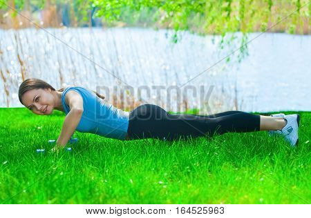 Beautiful woman athlete involved in sports on the street in a park conducting training with dumbbells in his hands and pushed off the floor.