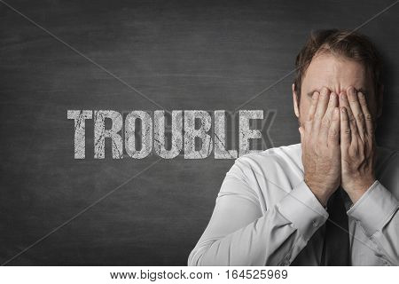 Trouble on black blackboard with sad businessman