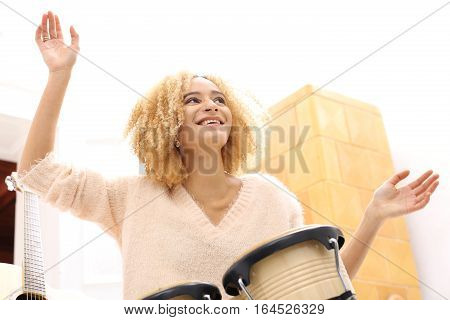 Music. Create your own music. Tapping the rhythm on the drums. Bongos, percussion. Girl playing bongo drums, small drums.