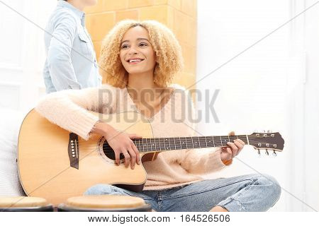 Acoustic guitar. Relax while playing the guitar. Girl playing the guitar. The girl guitar tunes.