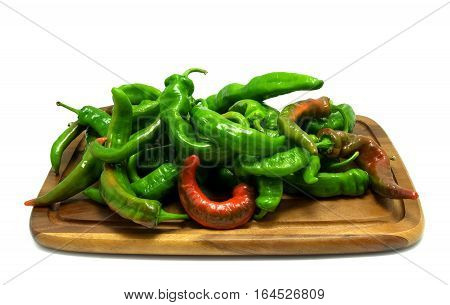 Multicolor hot peppers on wooden kitchen board. Isolated on white background.