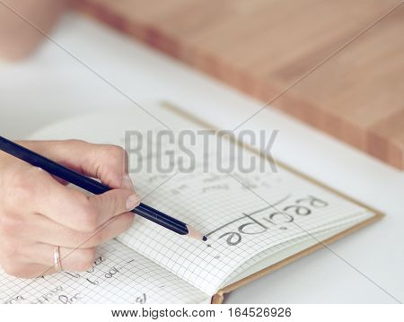 Young  woman standing in her kitchen writing on a notebook at home .