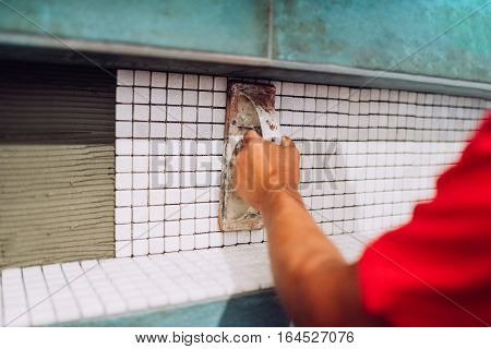 industrial male worker grouting mosaic ceramic tiles