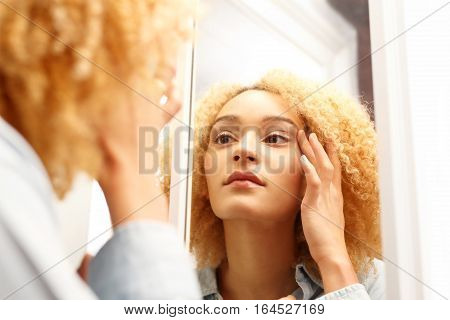 First wrinkles. The aging of the skin. Woman looks in the mirror watching for the first signs of aging.
