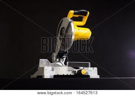 Compound miter power saw isolated on a black background.