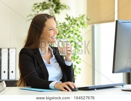 Happy businesswoman drinking water from a glass and looking through the window at office