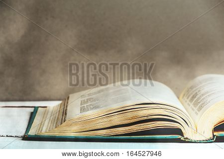 Old book with dust on wooden table or library desk, retro toned image