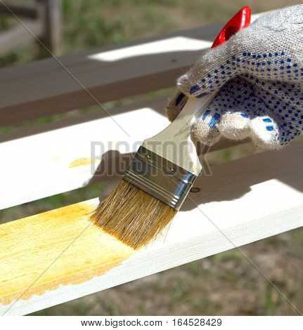 Hand in textile glove painting wooden shelving outdoors closeup view